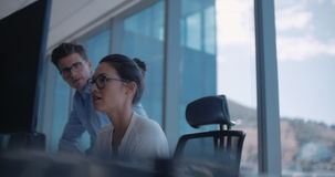 Business people working in office. Female manager working on computer and talking with male colleague in office. Business people working in office stock footage