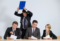 Business people working in office while frustrated businessman throwing clipboard Royalty Free Stock Photo