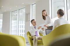 Business people working in office lobby stock images