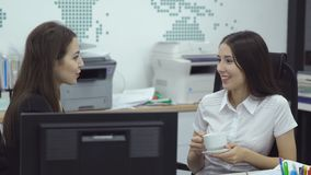 Business people working in office. Two young female office manager employees work with computers and talk during coffee breaks stock footage