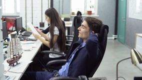 Business people working in office. Weekend is close. Young positive men in suit is sitting in the workplace and dreaming of vacation with his eyes closed against Stock Images