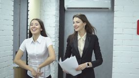Business people working in office. The work is done. Happy positive workers of large business center - two young girlin suit happily toss up papers rejoicing at stock video footage