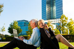 Business people working outdoors. He is working with laptop, she is calling someone on phone Royalty Free Stock Photo