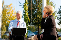 Business people working outdoors. He is working with laptop, she is calling someone on phone Royalty Free Stock Image