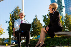 Business people working outdoors. He is working with laptop, she is calling someone on phone Stock Image