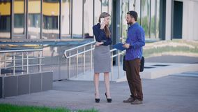 Business people are working outside. Female sales manager standing near office speaking on the telephone. Man dressed in. Business people are working outside stock footage