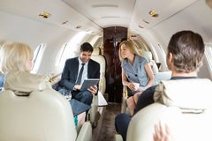 Business People Working In Private Jet. Businessman using digital tablet with colleagues in private jet Royalty Free Stock Images