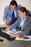 Business people working on statistics together Royalty Free Stock Image