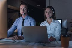 Business people working. Successful business people in headsets are using gadgets and smiling while working in office late at night Stock Image