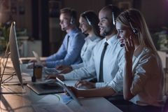 Business people working. Successful business people in headsets are using gadgets and smiling while working in office late at night Royalty Free Stock Photography