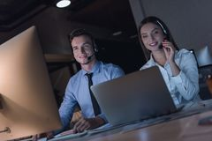 Business people working. Successful business people in headsets are using gadgets and smiling while working in office late at night Royalty Free Stock Images