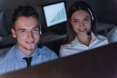 Business people working. Successful business people in headsets are using gadgets and smiling while working in office late at night Stock Images