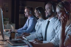 Business people working. Successful business people in headsets are using gadgets and smiling while working in office late at night Stock Photo