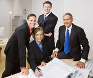 Business people working together. Business people looking over blueprints Stock Image