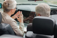 Business people working together on laptop in cabriolet. On a bright day Royalty Free Stock Images