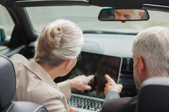 Business people working together on laptop in classy cabriolet. On a bright day Stock Photos