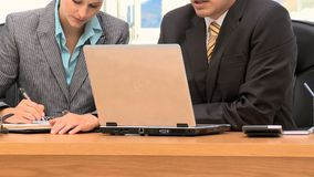 Business people working together with a laptop and a notepad. In an office stock video