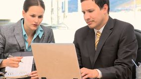 Business people working together on a laptop. In an office stock footage