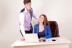 Business people working together on laptop in office at desk.  Royalty Free Stock Photos
