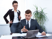 Business people working together on laptop in office at desk. Man and women working together on laptop in office at desk Stock Image