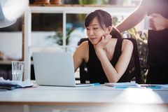 Business people working together on laptop in office. Shot of asian young women sitting at her desk working on laptop with male colleague standing by Stock Photography