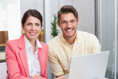 Business people working together on laptop and smiling. In the office Royalty Free Stock Photo