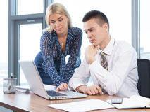 Business people working together  in office at desk. Business people working together on laptop in office at desk Royalty Free Stock Photo