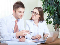 Business people working together  in office at desk. Business people working together on laptop in office at desk Royalty Free Stock Photos