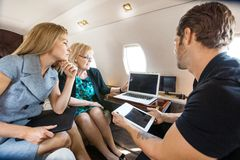 Business People Working Together In Private Jet. Business people working together on laptop and digital tablet in private jet royalty free stock photography