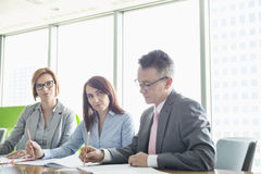Business people writing on books at conference table Stock Photography