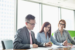 Business people writing on books at conference table royalty free stock photo