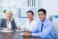 Business people writing on clipboards and looking at camera Royalty Free Stock Image