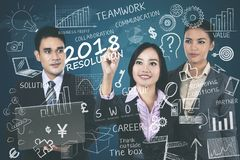 Business people writing resolution for 2018 Royalty Free Stock Images