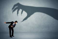 Business person afraid of a big monster claw shadow concept Royalty Free Stock Image