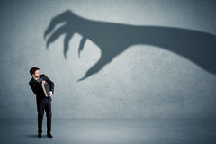 Business person afraid of a big monster claw shadow concept. On background Royalty Free Stock Photos