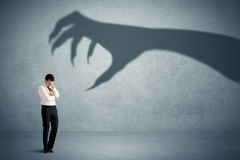 Business person afraid of a big monster claw shadow concept Stock Photos