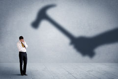 Business person afraid of a shadow hand holding hammer concept Stock Photo