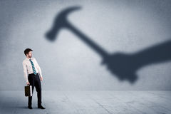 Business person afraid of a shadow hand holding hammer concept. On background Royalty Free Stock Images