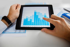 Business person analyzing financial statistics displayed on the tablet screen. Business person analyzing financial statistics displayed on the tablet Royalty Free Stock Image