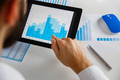 Business person analyzing financial statistics displayed on the tablet screen. Business person analyzing financial statistics displayed on the tablet Stock Image
