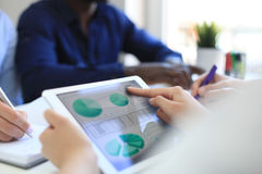 Business person analyzing financial statistics displayed on the tablet screen. Stock Image