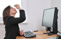 Business person applying eye drops. Detail of young business person (woman) applying eye drops on workplace - computer on table Stock Photos