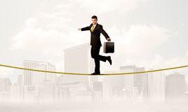Business person balancing on golden rope. A young elegant businessman walking on tight golden rope in front of city buildings landscape background concept Royalty Free Stock Images