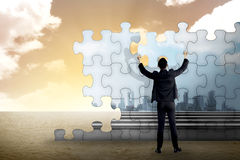 Business person building puzzle of city in the desert Stock Images