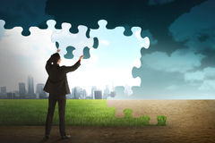 Business person building puzzle of city in the desert Stock Image