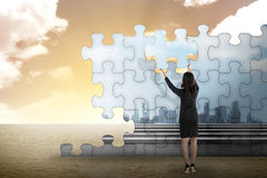 Business person building puzzle of city in the desert Stock Photography