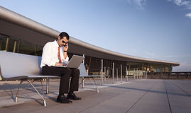 Business person busy on phone and laptop. stock photography