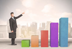 Business person climbing up on colourful chart pillars concept Stock Photo