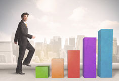 Business person climbing up on colourful chart pillars concept Royalty Free Stock Image