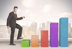 Business person climbing up on colourful chart pillars concept Stock Images